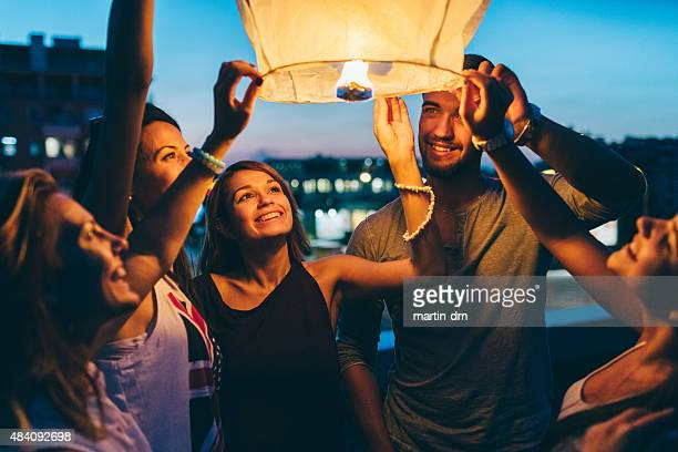 friends releasing paper lantern for new year - releasing stock pictures, royalty-free photos & images
