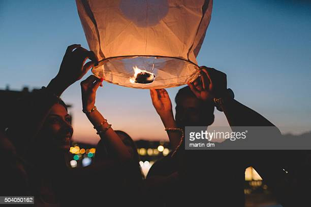 friends releasing paper lantern in the sky at night - releasing stock pictures, royalty-free photos & images