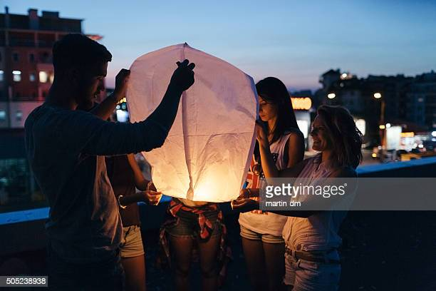 friends releasing paper lantern - releasing stock pictures, royalty-free photos & images