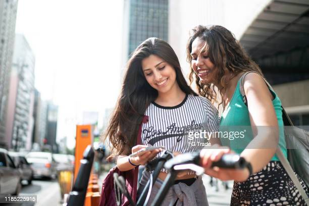 friends renting a bike - sharing economy stock pictures, royalty-free photos & images