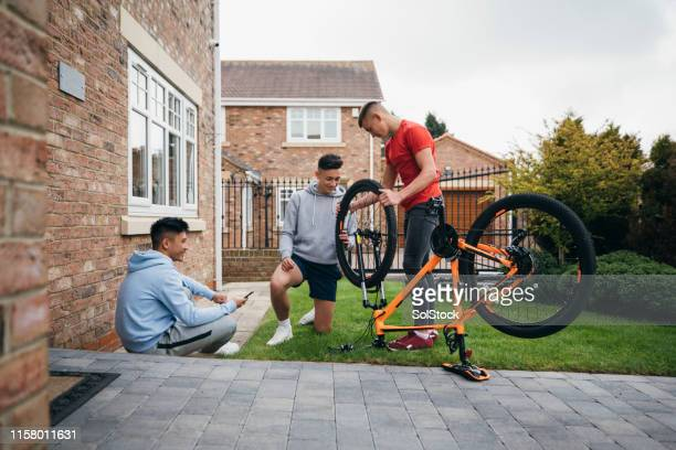 friends repairing a mountain bike - teenager stock pictures, royalty-free photos & images