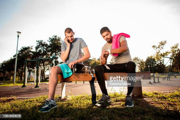 Friends resting after exercise in outdoor gym
