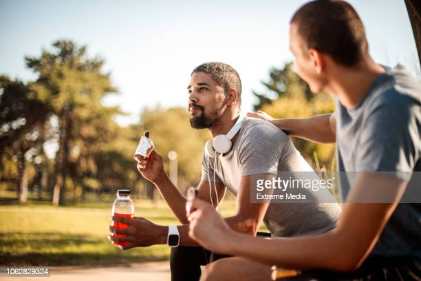 friends resting and hydrating after exercise - energy drink stock pictures, royalty-free photos & images