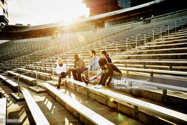 Friends resting during workout in stadium