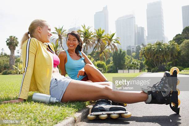 friends resting in park after rollerblading - inline skating stock pictures, royalty-free photos & images