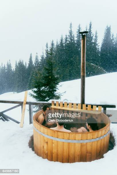 Friends resting in wooden hot tub