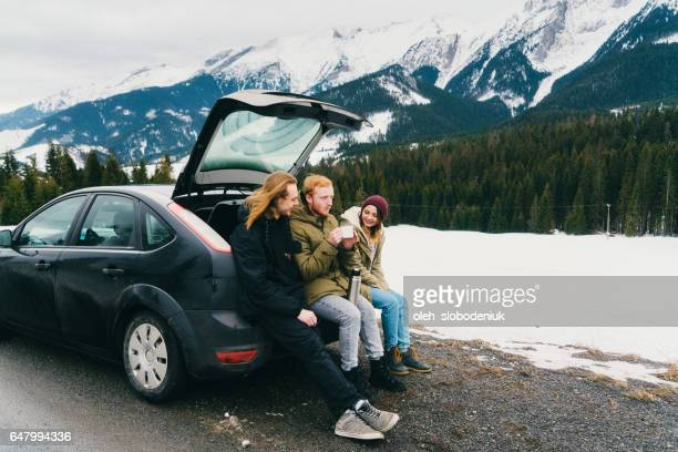Friends resting near the car in mountains in winter