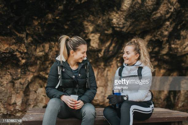 friends resting under shelter in the mountain and drinking hot tea - sheltering stock pictures, royalty-free photos & images