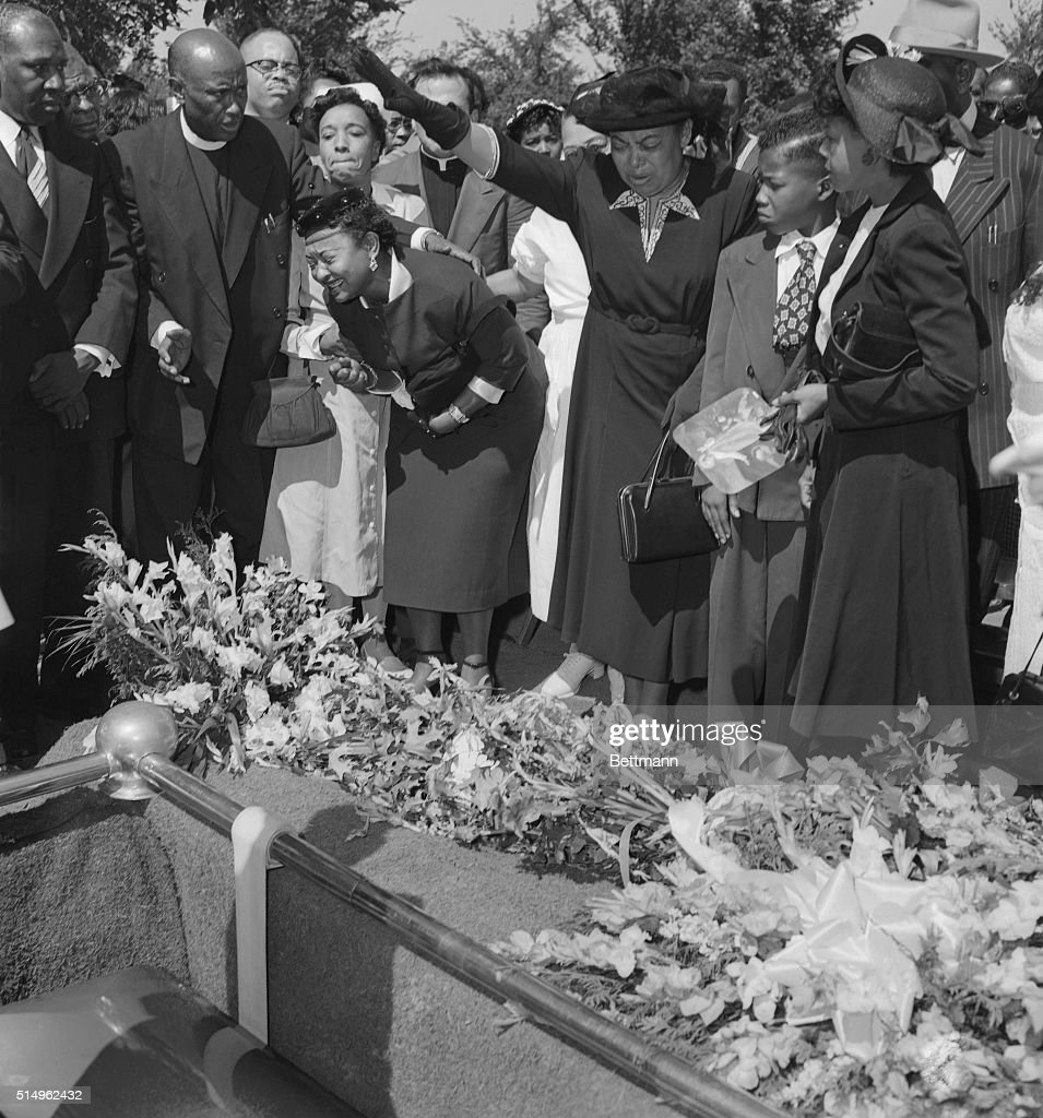 Friends restrain grief-stricken Mrs. Mamie Bradley (left) as her son's body is lowered into the grave after a four day, open casket funeral. The 15-year old Negro youngster, Emmett Till, was shot and clubbed to death last week in Greenwood, Mississippi. He is believed to have been murdered for allegedly whistling at a white woman. Two men have confessed kidnapping the youth by deny killing him.