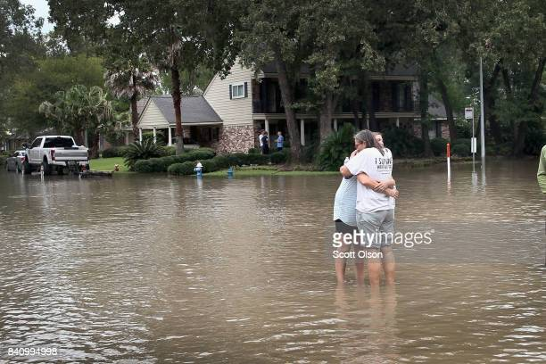 Friends reunite in the middle of a flooded intersection as water continues to rise in their neighborhood following Hurricane Harvey on August 30,...