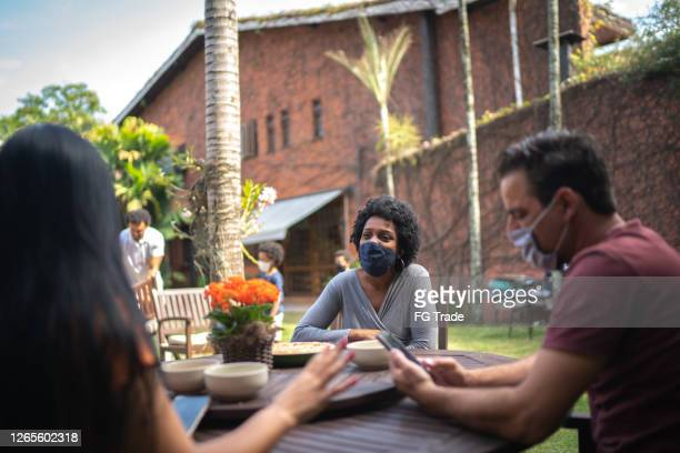 friends reunited in the backyard, talking and using smartphone - social event stock pictures, royalty-free photos & images