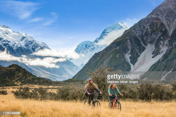 friends ride bikes through the mount cook national park. - nueva zelanda fotografías e imágenes de stock