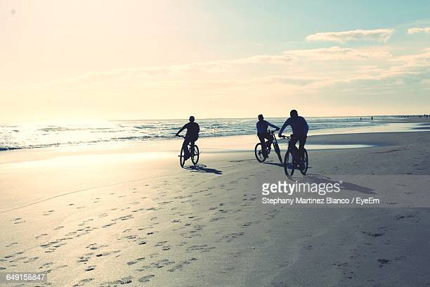 Friends Riding Bicycles At Beach Against Sky