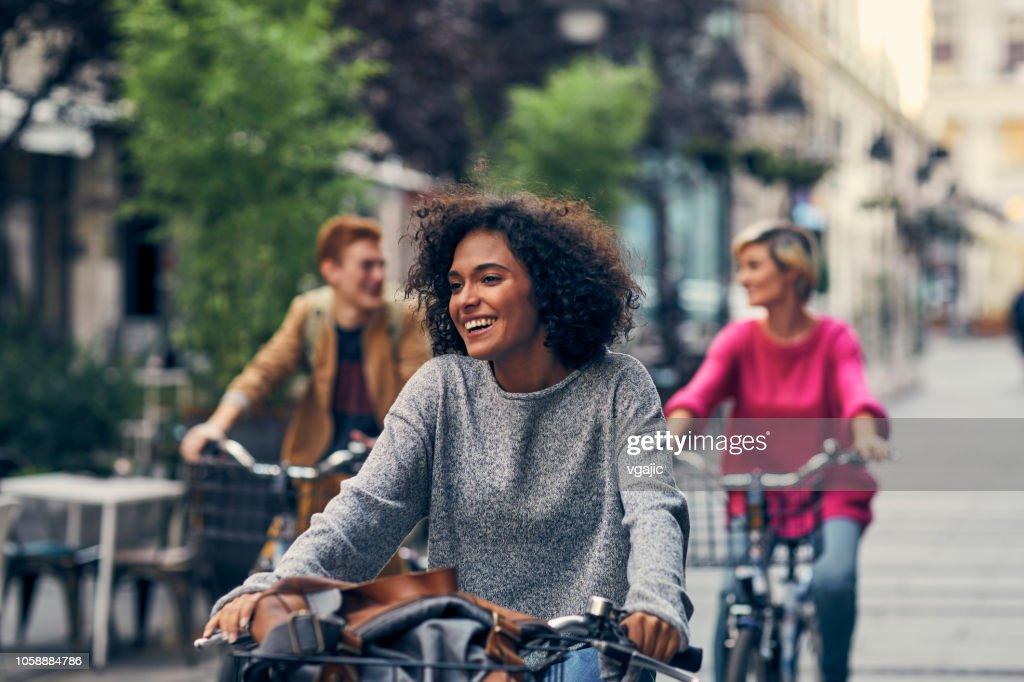 Vrienden paardrijden fietsen In een stad : Stockfoto