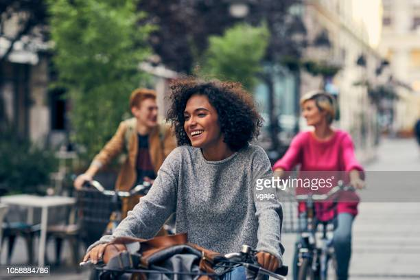 friends riding bicycles in a city - cycling stock pictures, royalty-free photos & images