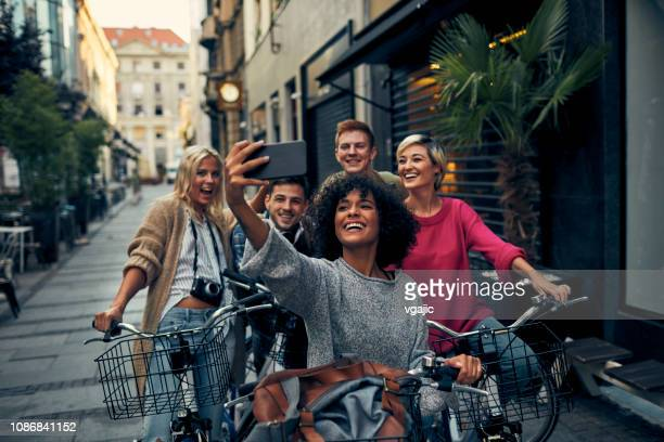friends riding bicycles in a city - generation z stock pictures, royalty-free photos & images