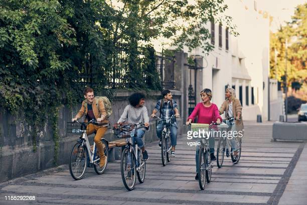 freunde fahren fahrräder in einer stadt - pedalantrieb stock-fotos und bilder