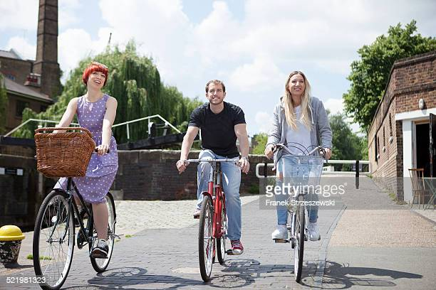 friends riding bike along canal, east london, uk - east london stock pictures, royalty-free photos & images