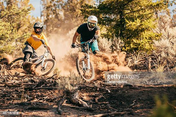 Friends riding bikes on a dusty trail.