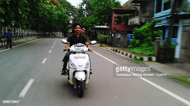 Friends Riding Motor Scooter On Street