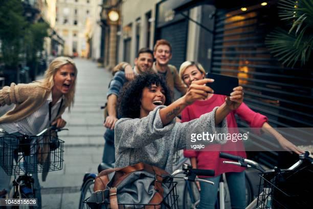 freunde fahren vermietet fahrräder in einer stadt - fotohandy stock-fotos und bilder