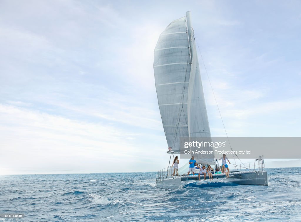 Friends riding sail boat in water : Stock Photo