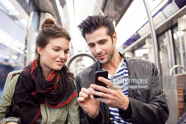 Friends riding subway looking at smartphone together