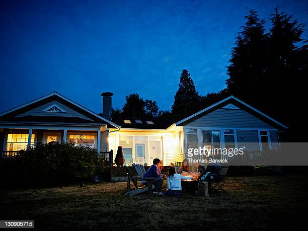 friends roasting hot dogs over fire at dusk - bonfire stock pictures, royalty-free photos & images
