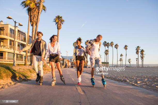friends roller skating on the boardwalk in venice beach - santa monica promenade - los angeles, usa - santa monica stock pictures, royalty-free photos & images