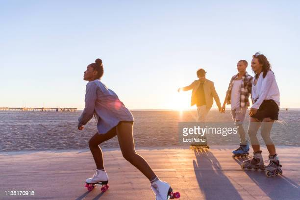friends roller skating on the boardwalk in venice beach - santa monica promenade - los angeles, usa - inline skating stock pictures, royalty-free photos & images
