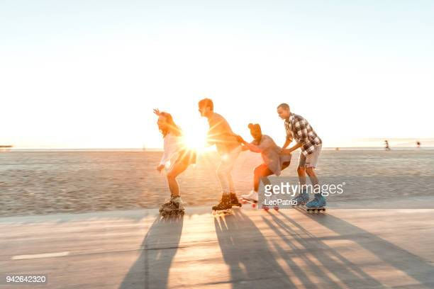 friends roller skating on the boardwalk in venice beach - santa monica promenade - los angeles, usa - roller skating stock photos and pictures