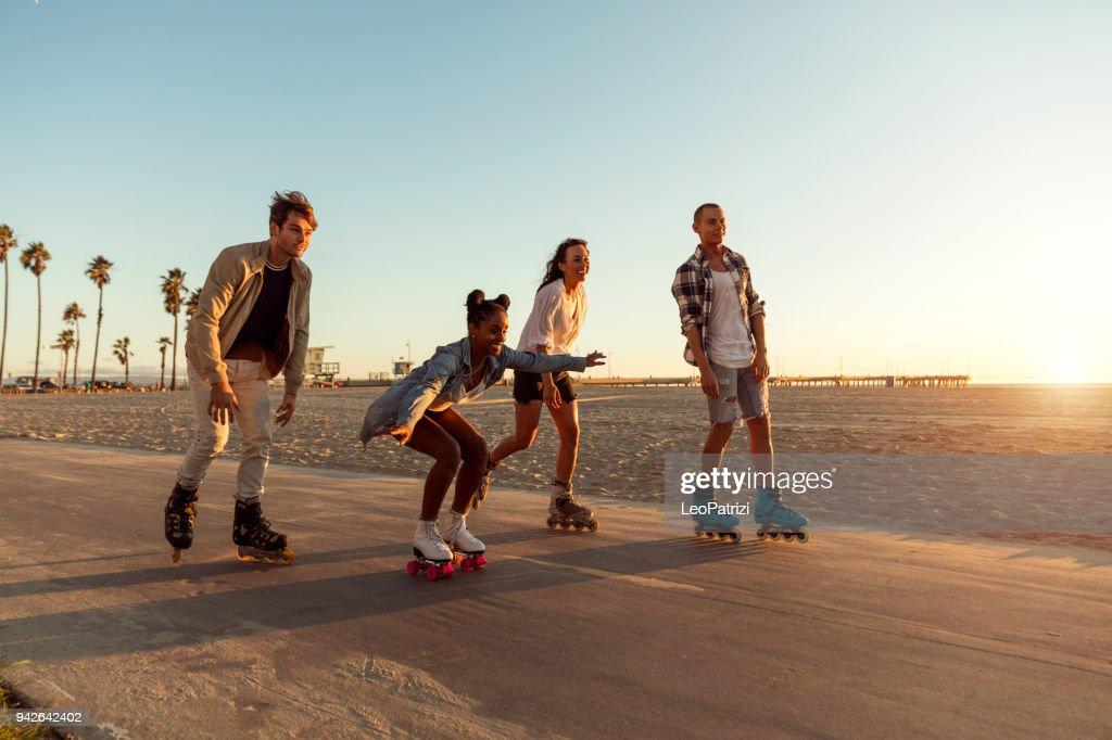 Friends roller skating on the boardwalk in Venice Beach - Santa Monica promenade - Los Angeles, USA : Stock Photo