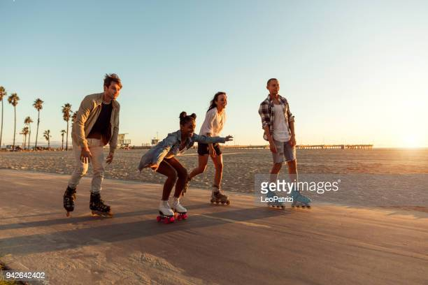 friends roller skating on the boardwalk in venice beach - santa monica promenade - los angeles, usa - venice foto e immagini stock