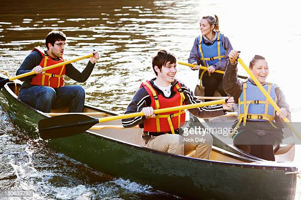 friends rowing canoes on still lake - water sport stock photos and pictures