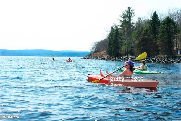 Friends rowing kayaks in lake