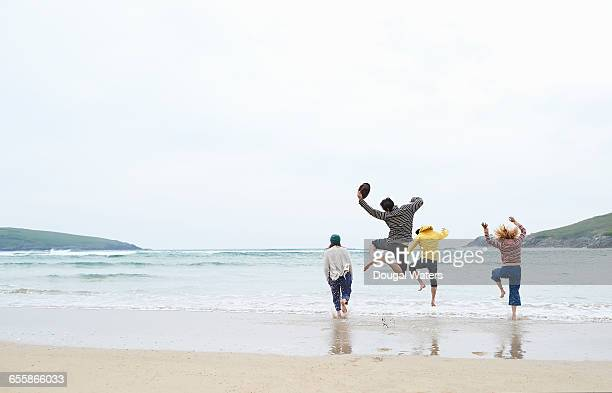 Friends run and jump into sea at beach.