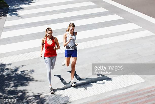 Amigos correndo urban faixa de pedestres
