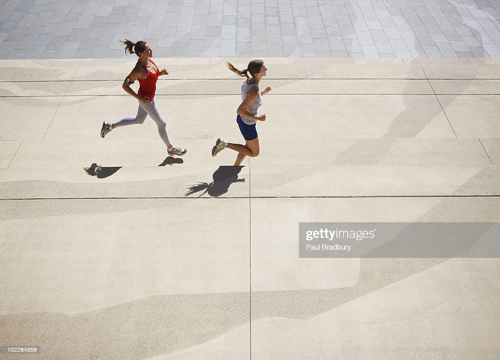 Friends running along urban sidewalk : Stock Photo
