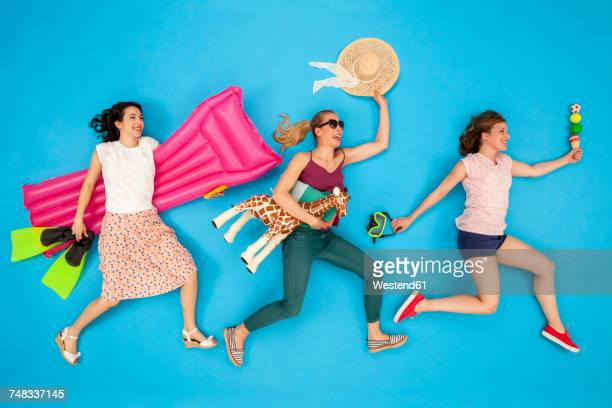 friends running and laughing with holiday accessories under their arms - white giraffe stockfoto's en -beelden