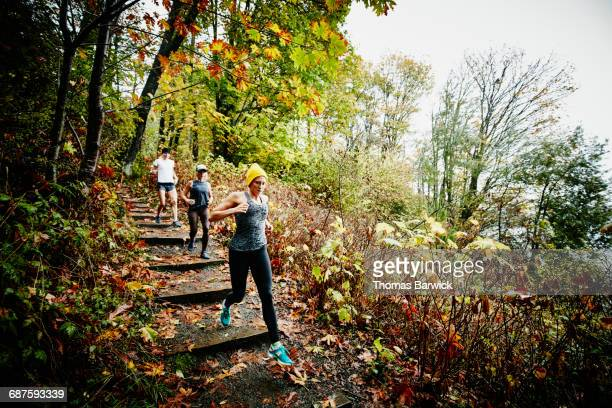 Friends running down stairs on trail in park