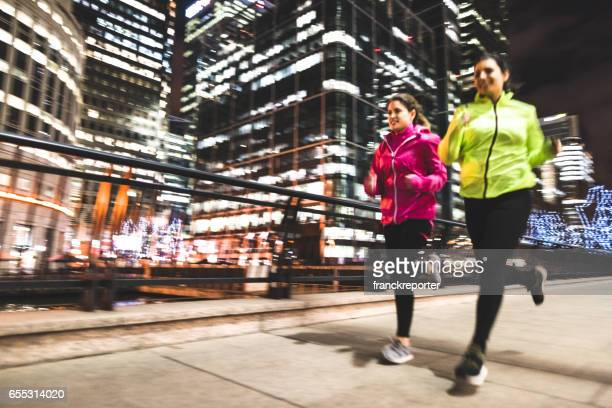 friends running in london in canary wharf