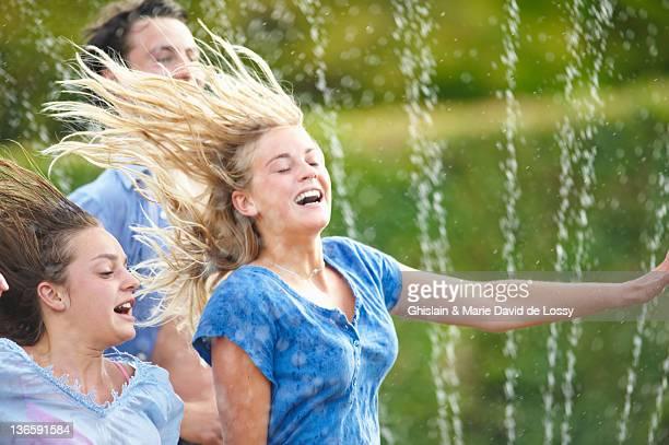Friends running in sprinkler