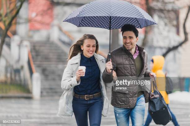Friends running in the city on a rainy day