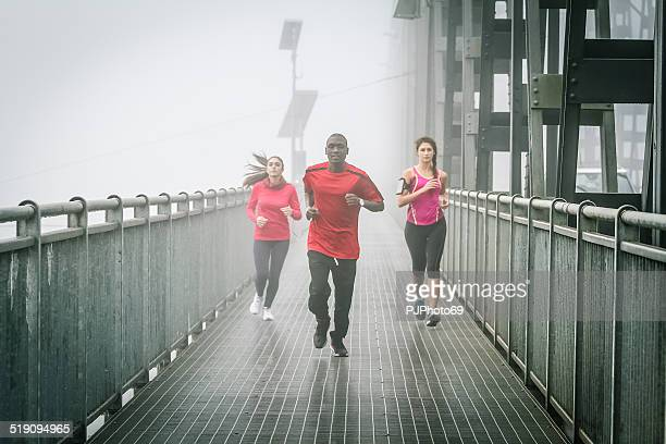 friends running in the fog on iron bridge - pjphoto69 stock pictures, royalty-free photos & images