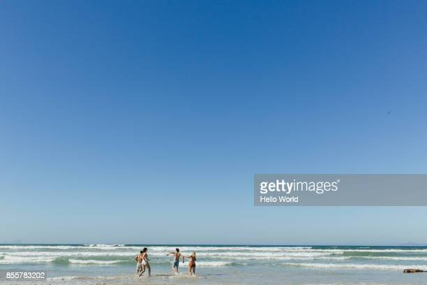 friends running in the waves. wide shot - blue stock pictures, royalty-free photos & images