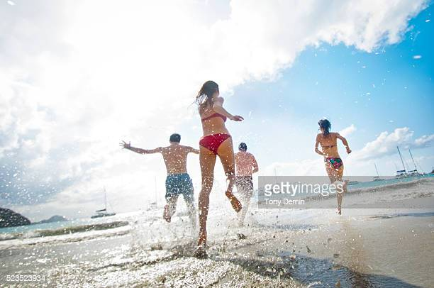 friends running into sea - cane garden bay stock pictures, royalty-free photos & images