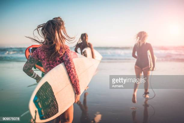 friends running into the ocean with their surfboards - morning stock pictures, royalty-free photos & images