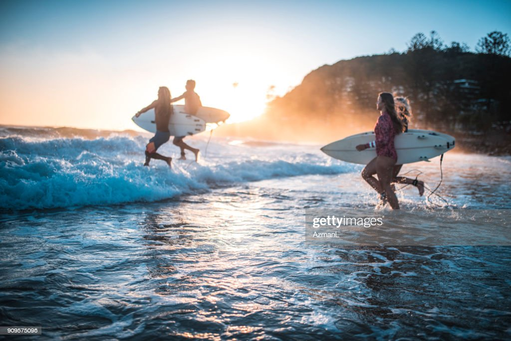 Friends running into the ocean with their surfboards : Stock Photo