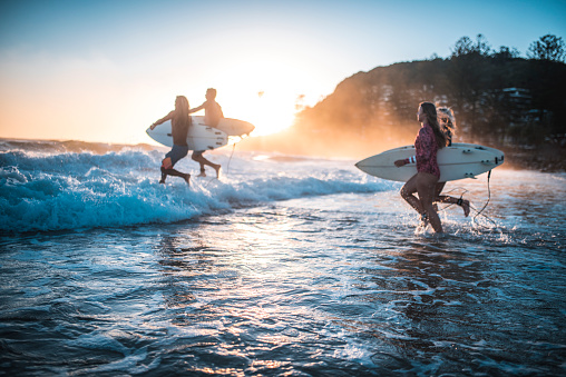 Friends running into the ocean with their surfboards - gettyimageskorea
