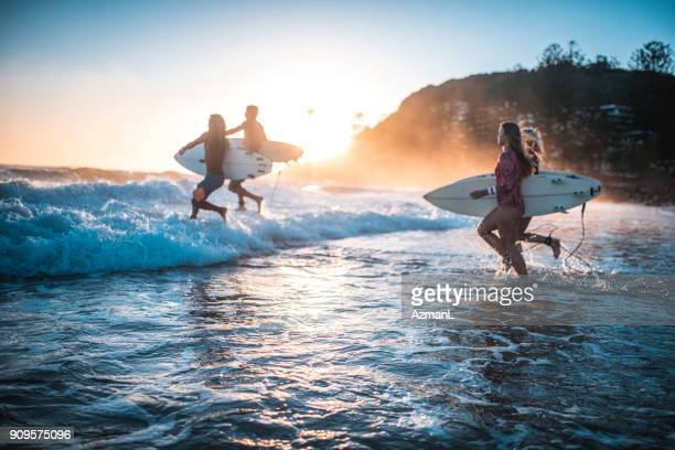 friends running into the ocean with their surfboards - friendship stock pictures, royalty-free photos & images